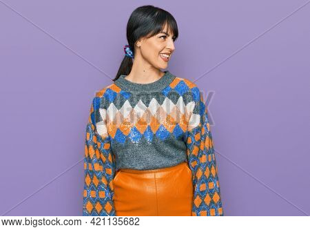 Young hispanic woman wearing casual clothes looking away to side with smile on face, natural expression. laughing confident.