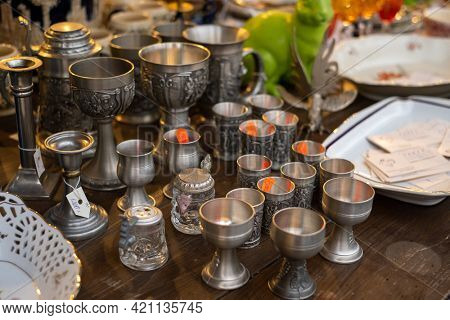 High angle of assorted silver goblets placed on wooden stall at local souvenir bazaar
