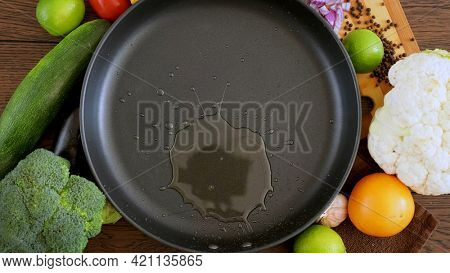 Cook pours sunflower oil into a frying pan, top view. Kitchen pan stands on brown boards, vegetables around it, and oil is poured into it for frying.