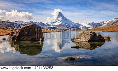 Famous alpine peak Matterhorn reflected in a pond in the Swiss Alps
