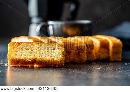 Sliced sponge dessert. Sweet sponge cake on black table.