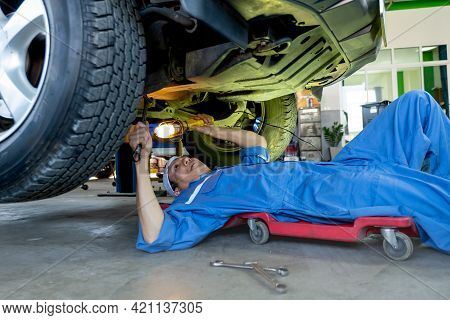 Technician Or Garage Worker Lie Down Under The Car And Use Lantern To Guide For Fix The Problem In W