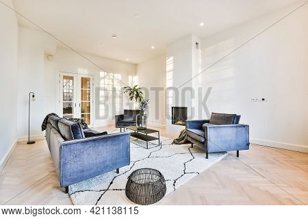 Contemporary Cozy Armchairs And Sofa On Soft Carpet In Light Modern Living Room With Minimalist Fire