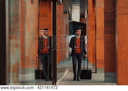 Going to airport terminal. Confident businessman traveler walking on city streets and pulling his suitcase drinking coffee and speaking on smartphone