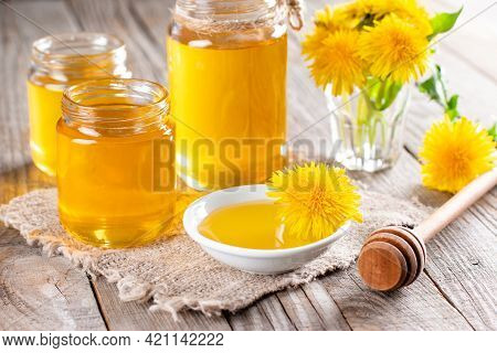 Homemade Healthy Dandelion Syrup In A Glass Bottle, Decorated With Fresh Flowers On Rustic Wooden Ba