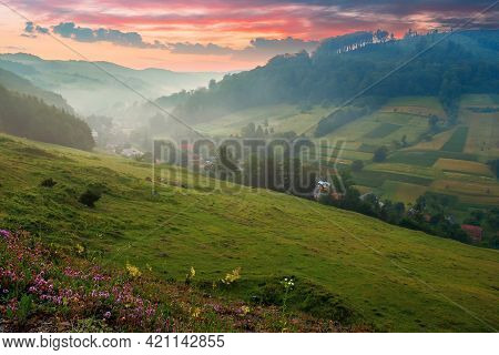 Valley On The Misty Morning. Village In The Distance. Grass And Flowers On The Hill In Morning Light