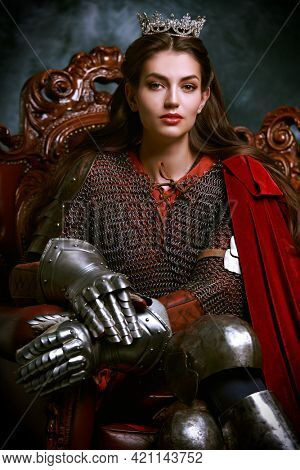 Portrait of a beautiful medieval queen in knightly armor sitting on a throne. History of the Middle Ages.
