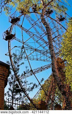 Detailed View Of Abandoned Ferris Wheel. Old Abandoned Rusty Metal Ferris Wheel Against Blue Sky In
