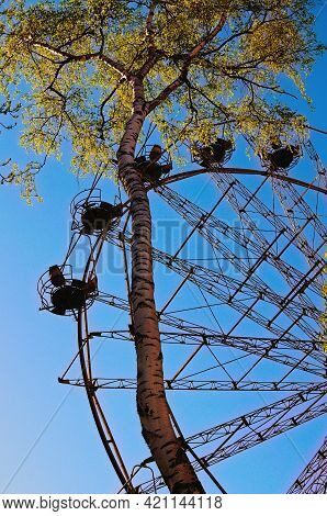 Close-up View Of Abandoned Ferris Wheel. Old Abandoned Rusty Metal Ferris Wheel Against Blue Sky In