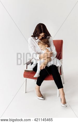 A Beautiful Young Mother Holds Her Adorable Daughter In Her Arms, Hugging Her. Mom Gently Kissing An