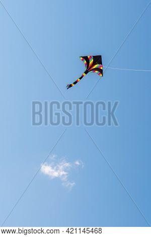 Multicoloured One-string Stunt Kite Against Sky. Delta-shape Kite
