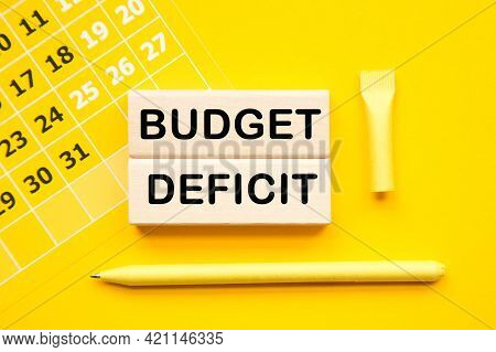Budget Deficit. Calendar And Wooden Bars With Informationon On The A Yellow Background Desktop .