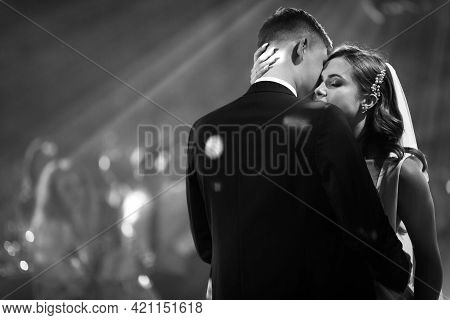 Portrait Of Newlyweds First Wedding Dance. Just Married Couple Dancing In Darkness. Groom Holds Brid