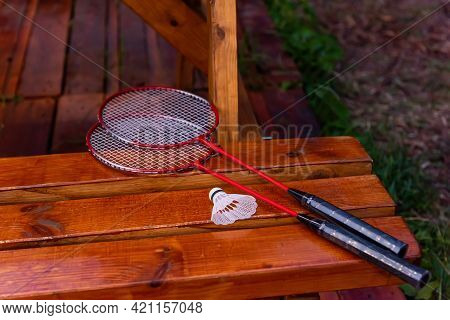 On A Wooden Table Lie Two Red Badminton Rackets With A White Shuttlecock. Active Games, Sports At A