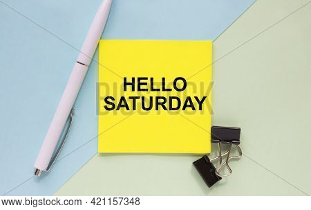 Top View Of A Business Card With Text Hello Saturday, Pen, Paper Clips On A Colored Background. Busi