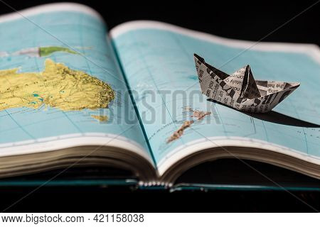 Paper Boat On The Atlas Of The World. Open Book. Travel Dreams. Creative Image.