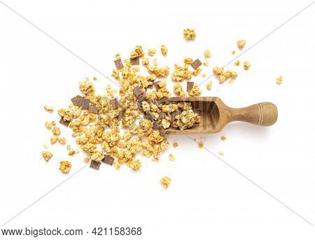 Crunchy granola, muesli pile with chocolate in wooden spoon on white background