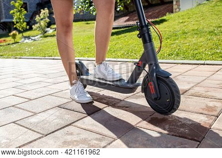 Shot Of A Young Person Legs And Calves As They Stand On The Electric Kick Scooter