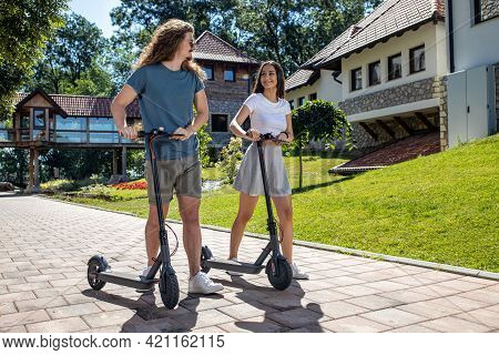 Young Man And A Young Woman Having Fun Outdoors As They Try Their New Scooters