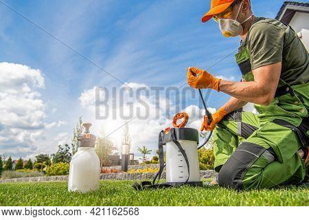 Caucasian Worker In His 40s Preparing Pest Control Spraying Equipment. Spring Garden Maintenance The