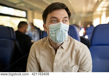 Man Traveling By Train Wearing A Facemask. Social Distancing When Traveling By Railway During Covid-