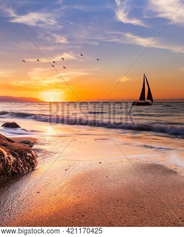 A Sailboat Sails Along The Ocean At Sunset In Vertical Image Format