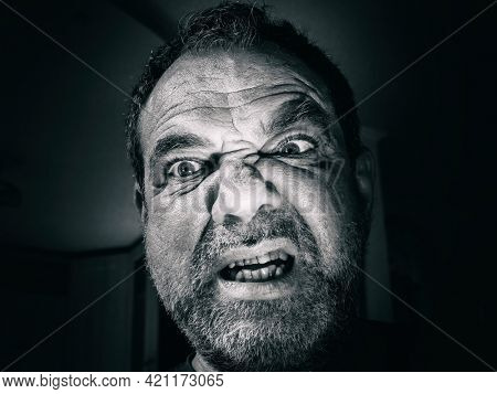 Angry aggressive man close-up face in the dark