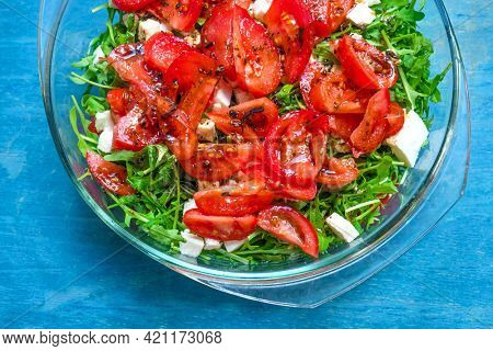 Salad with fresh arugula, tomatoes, goat cheese and olive oil. Vegan healthy food.