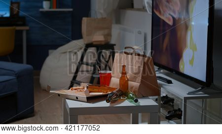 Close Up Of Table With Food And Booze Leftover On Misery Table In Empty Unorganized Dirty Living Roo