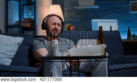 Hopeless Depressed Man Listening Sad Music At Headphones, Sitting Alone Frustrated, Stressed On Sofa