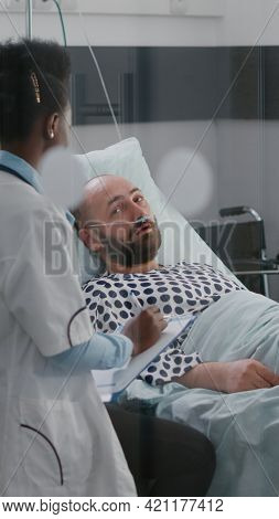 Afro American Doctor Checking Sick Man Monitoring Sickness Symptom During Recovery Appointment In Ho