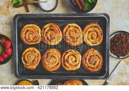 Fresh baked cinnamon buns on black iron tray. Top view