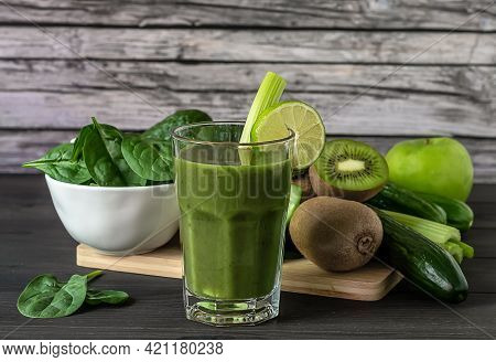 Glass Of Fresh Organic Green Smoothie With Spinach, Cucumber, Kiwi, Celery, And Avocado On Wooden Ba