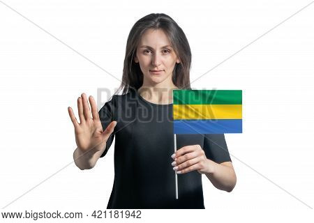 Happy Young White Woman Holding Flag Of Gabon And With A Serious Face Shows A Hand Stop Sign Isolate
