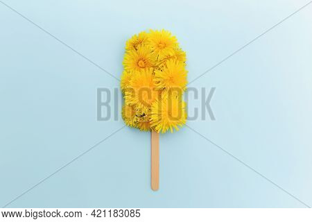 Greeting Card Concept Flat Lay On Blue Background With Dandelion Blossom Ice Cream Lolly On A Stick.