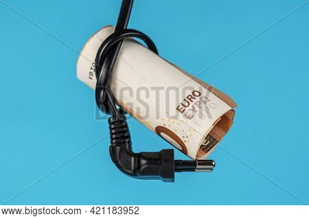 Cash Euro Money And Electrical Plug Close Up On A Blue Background. Creative Concept Of Energy Effici