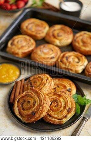 Delicious, fresh baked cinnamon buns served on black ceramic plate. With various sides