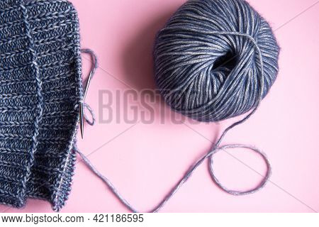 Knitting Project Underway. Knitting With A Ball Of Blue Yarn And Knitting Needles On Pink Background