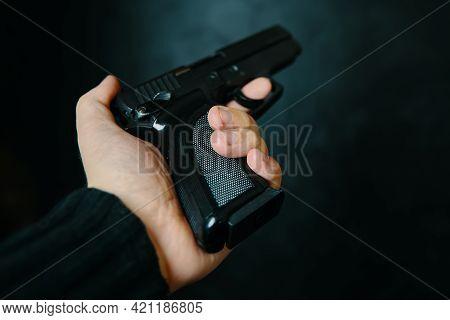 Criminal Holding Pistol On Dark Background. First Person View Of Gun. Firearm In Mans Hand. Defense
