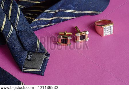 Blue Tie With Yellow Stripes, Gold Ring And Cufflinks On A Pink Background. Male Accessories.