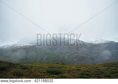 Minimalist Alpine Landscape With Snow-capped Mountains In Overcast Weather In Rain. Deep Gorge On Ba