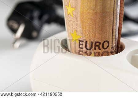Fifty Euro Banknote In A White Extension Cord Outlet On The Background Of Wires And Plug In Blur. Ma