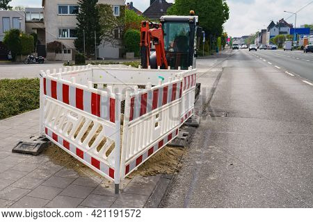 Red And White Fence During Repair Work On A City Road. Small Excavator In The Background. Cars Drive