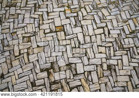 Grey Paving Slabs Made Of Natural Stone Laid With A Herringbone Pattern. View From Above. Close Up.