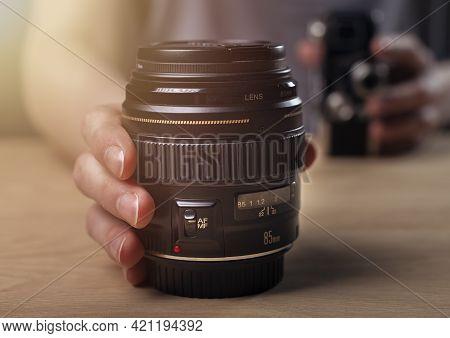 Photographer Showing Camera Lens, Blurred Vintage Old One And Modern 85 Mm Portrait Lens.
