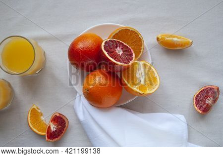 Sweet And Juicy Blood Oranges And Oranges, Whole And Cut On A White Plate And Glasses Of Fresh Orang