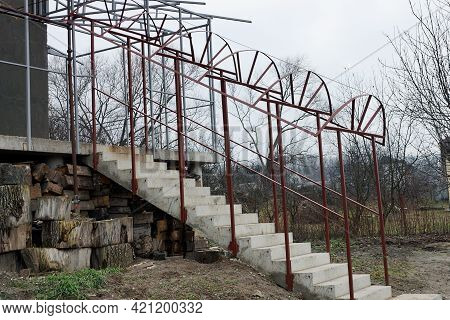 Unfinished Veranda Of Gray Concrete Steps Of A Staircase With Brown Iron Railings Near The House On