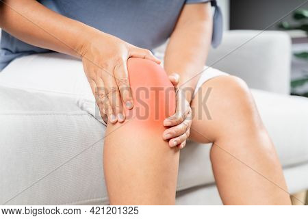 Close Up Of Chubby Woman Sitting On The Sofa And Feeling Knee Pain And She Massages Her Knee. Health