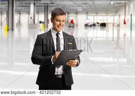 Airport male attendant writing a document inside a terminal building hall
