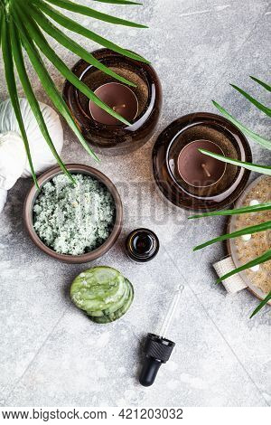 Set Of Natural Skin Care Products And Palm Leaves On A Grey Background. Massage Stones, Essential Oi